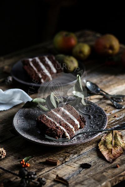 Autumn mood: slices of chocolate & pear cake on wooden table