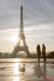 Couple of tourists looking at Eiffel tower at sunrise, Paris
