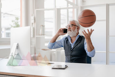 Mature man on cell phone at desk playing with basketball