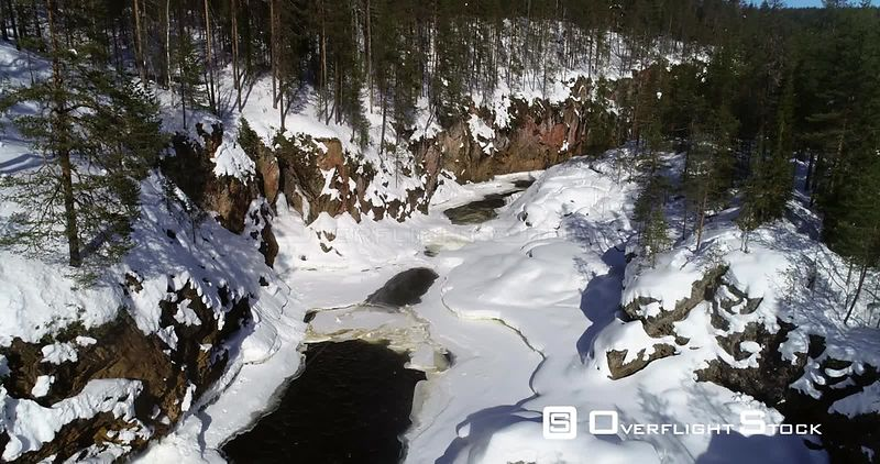 Lapland rapids, aerial rising drone view of kiutakongas rapid, in Oulanka national park, on a sunny winter day, in Kuusamo, PohjoisPohjanmaa, Finland