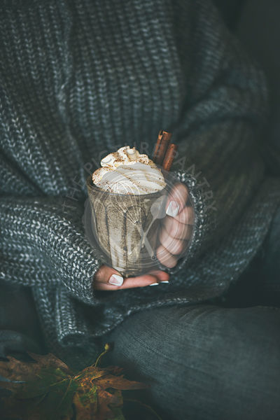 Woman in grey woolen sweater with mug with hot chocolate