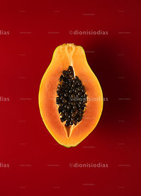 Sliced papaya in half on red background