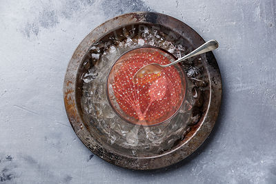 Red caviar in glass bowl on ice in metal plate on concrete background