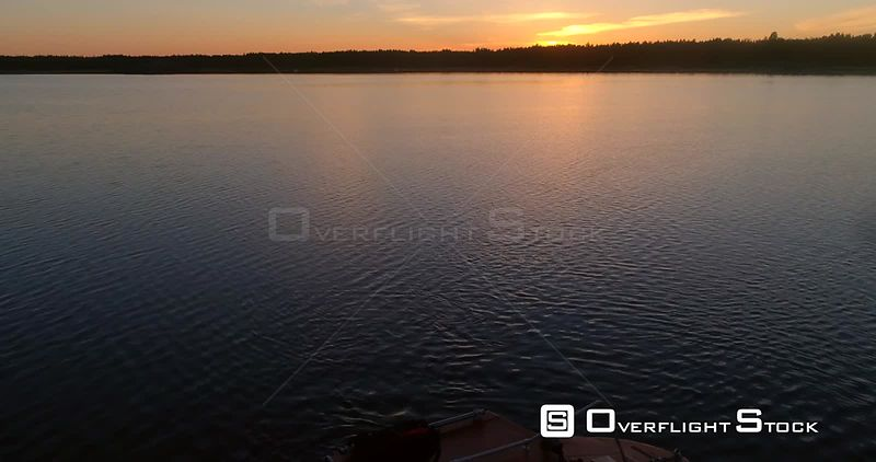 Boat at a calm sea, aerial view of a calm sunset and over a boat in the clear reflecting waters of baltic sea, on a sunny summer evening dusk, in Hanko, Finland