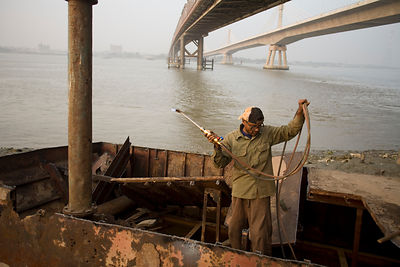 Bangladesh - Chittagong - A man dismantles a boat with a blow torch and hammer on the banks of the Karnaphuli River beneath the Kalurghat Bridge