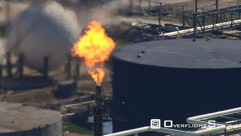 Aerial zoom-out from flare stack to oil refinery view