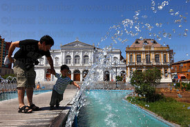 Boy playing with fountain spray , Municipal Theatre in background , Plaza Prat , Iquique , Chile