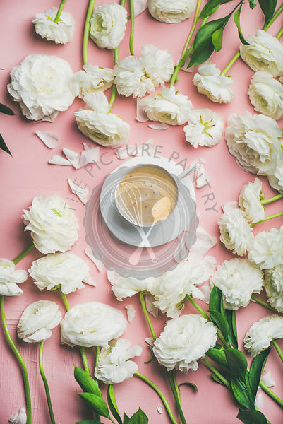 Flat-lay of cup of coffee surrounded with white ranunculus flowers