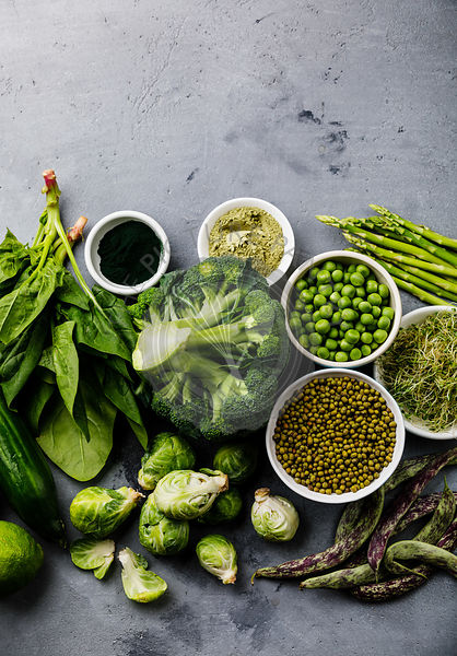 Healthy Green food Clean eating selection Protein source for vegetarians: asparagus, brussels sprouts, broccoli, spinach, spirulina, green peas on gray concrete background copy space