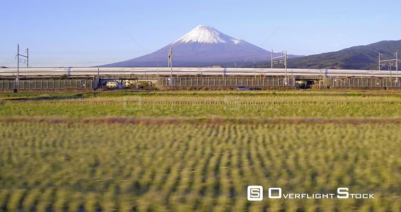 Panning shot of a Shinkansen bullet train passing through harvested rice fields, with Mount Fuji in the background, Honshu, Japan, November 2017.