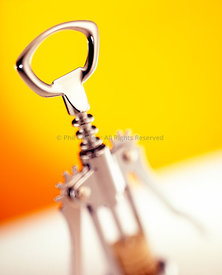 corkscrew bottle opener on yellow and white background