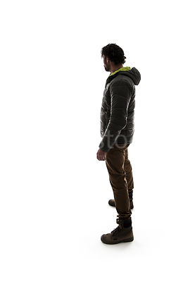 A man in outdoor clothing, looking away, in silhouette – shot from eye level.