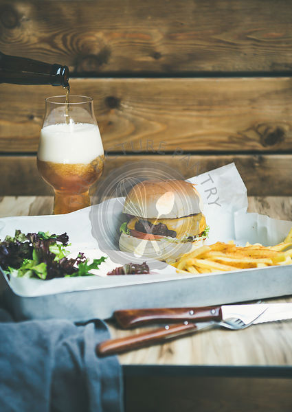 Beef burger, french fries, salad and glass of beer