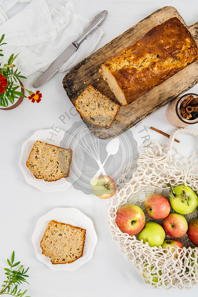 Cinnamon apple bread sliced on a wooden cutting board photographed from top view. Apples in a net bag and apple bread slices on two plates accompany.