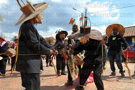 Achus (masked old men figures) giving alcohol to wooden horse during festival parade, San Ignacio de Moxos, Bolivia