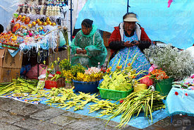 Women messaging using mobile phones on stalls selling Easter eggs and ornaments and crosses made out of palm leaves on Palm Sunday, La Paz, Bolivia