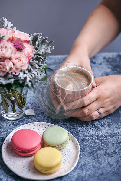 Woman holding a cup of coffee and eating macarons for dessert