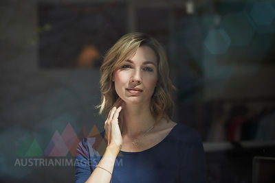 Portrait of blond woman behind window pane, hand on neck