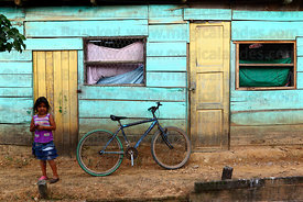 Girl and bicycle propped against wall of typical wooden house , Rurrenabaque , Bolivia