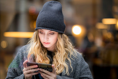 Portrait of serious young woman using smartphone