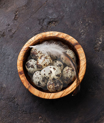 Olive wood bowl with fresh quail eggs on dark background
