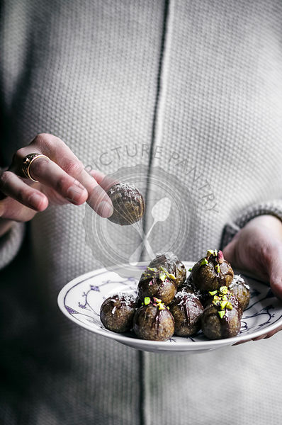 Raw vegan date almond truffles being help by a woman