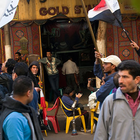 A crowd demonstrating against the Morsi government passes the Gold Star cafe, Cairo