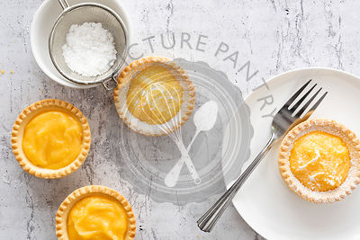 A lemon tartlet on a plate with a fork and lemon tartlets with a bowl of powdered sugar.