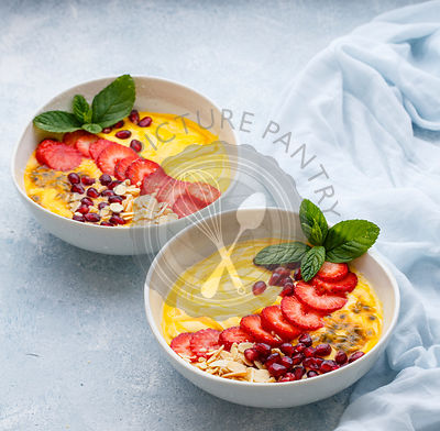 Mango Passion fruit Smoothie Bowl topped with strawberries, pomegranate, passionfruit and almond flakes.