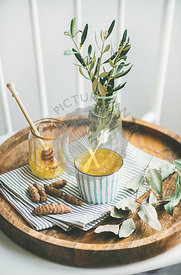 Healthy vegan turmeric latte or golden milk with honey in striped cup on wooden tray