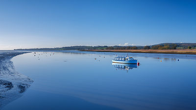 Turf Ferry moored on a mirror calm River Exe at Topsham, Devon, UK