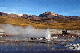 Geyser erupting and machinery from old geothermal power project, El Tatio geyser field, Region II, Chile