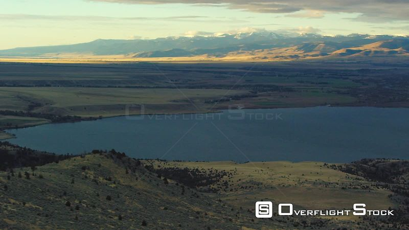 The dawn sun highlights the golden autumn colors of the Madison Valley and Ennis Lake in Southwestern Montana, as the Gravelly mountain range rises in the distance