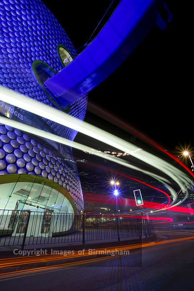 The Selfridges building at the Bullring Shopping Centre, at night with traffic trails. Birmingham, England, UK