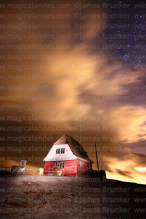 Wind blown cloud above old ski hut on Mt Chacaltaya at night, Bolivia