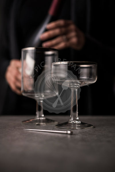 Antique, high end wine glasses with sommelier in background with bottle of red wine.
