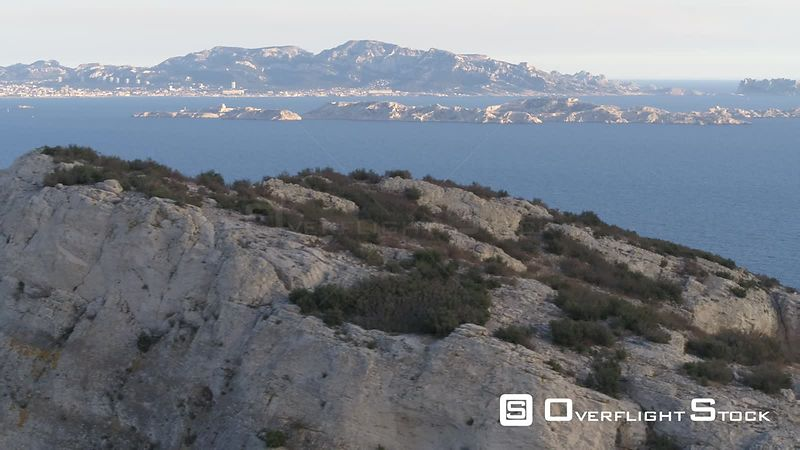 Aerial view of Calanque La Vesse and the Mediterranean Sea with Frioul islands in the background , filmed by drone, France