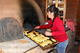 Woman cooking empanadas in an earth oven , Pisac , near Cusco , Peru