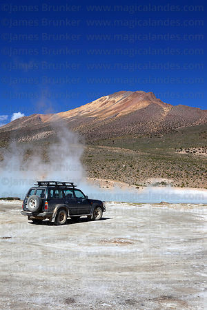 Toyota Land Cruiser parked next to hot springs at Polloquere and Cerro Capitan peak , Salar de Surire , Region XV , Chile
