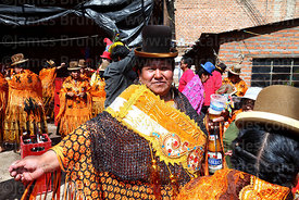 Cholita drinking at street party after formal parades, Virgen de la Candelaria festival, Puno, Peru