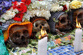 Skulls with burning candle and coca leaf offerings at Ñatitas festival, La Paz, Bolivia