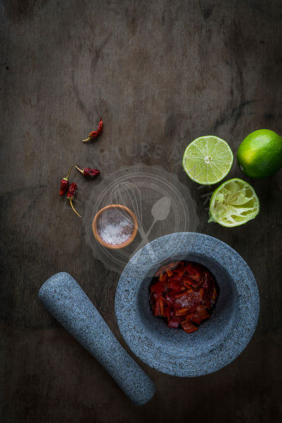 Mortar and pestle with ingredients for chili paste. Top view