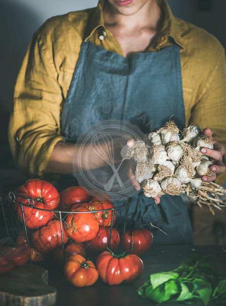 Woman in apron holding bunch of garlic for cooking