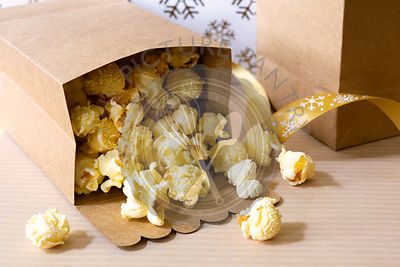 Maple butter popcorn spilling out from a paper bag.