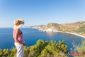 Woman looking at the coastline from lookout. Kefalonia, Greek Islands, Greece