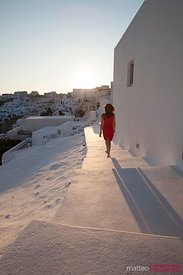Woman in red walking at sunset in Oia, Santorini, Greece