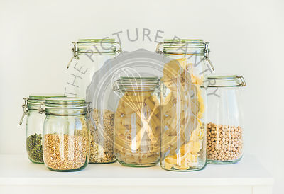 Various uncooked cereals, grains, beans and pasta for healthy cooking in glass jars on kitchen shelf