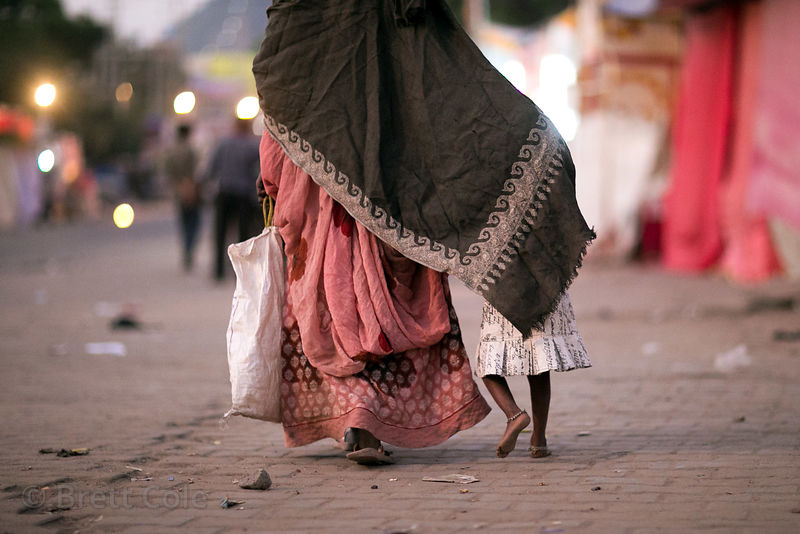 A mother walks with her daughter under her wing in Pushkar, Rajasthan, India