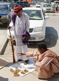 An arab man buys ammunition for his gun in the street, Salalah, Oman