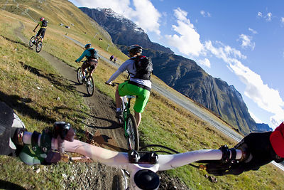 Italy, Livigno, View of woman and man riding mountain bike downhill